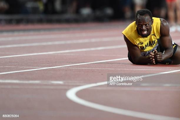 TOPSHOT Jamaica's Usain Bolt reacts after pulling up injured in the final of the men's 4x100m relay athletics event at the 2017 IAAF World...