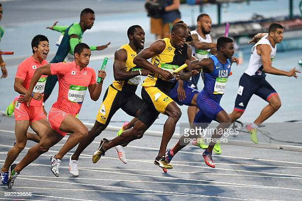 TOPSHOT Jamaica's Usain Bolt receives the baton from Jamaica's Nickel Ashmeade during the Men's 4x100m Relay Final during the athletics event at the...