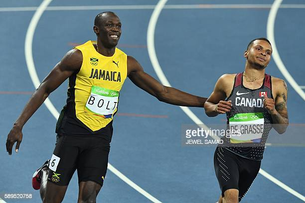 TOPSHOT Jamaica's Usain Bolt smiles next to Canada's Andre De Grasse after they competed in the Men's 100m Semifinal during the athletics event at...