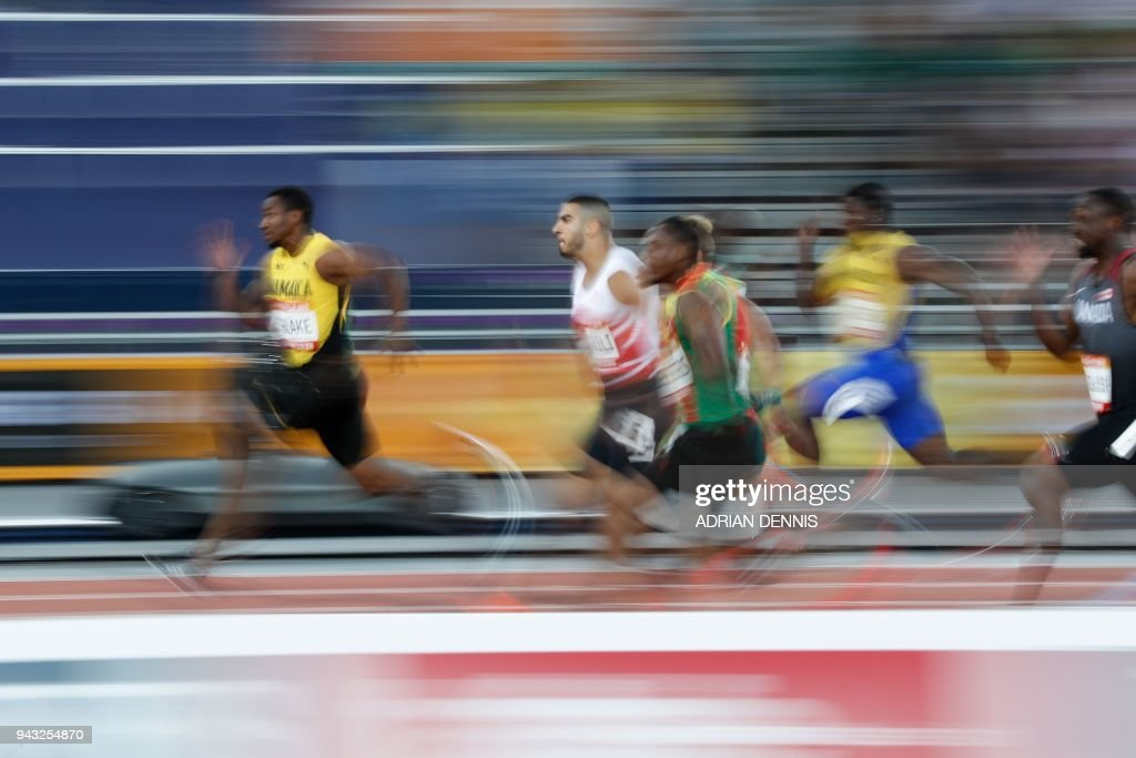 TOPSHOT - Jamaicas Yohan Blake (L) competes in the athletic's men's 100m semifinal during the 2018 Gold Coast Commonwealth Games at the Carrara Stadium on the Gold Coast on April 8, 2018. / AFP PHOTO / Adrian DENNIS