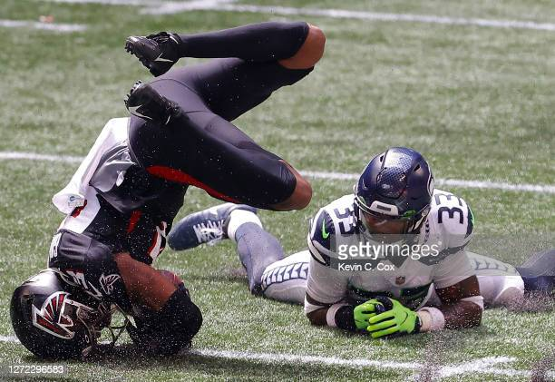 Jamal Adams of the Seattle Seahawks tackles Russell Gage of the Atlanta Falcons after a reception in the first half at Mercedes-Benz Stadium on...