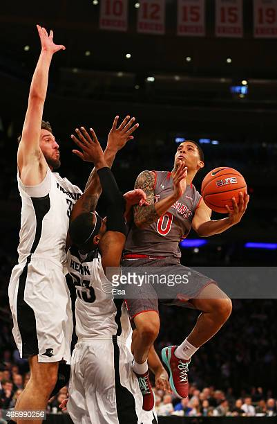 Jamal Branch of the St John's Red Storm heads for the net as Carson Desrosiers and LaDontae Henton of the Providence Friars defends during a...