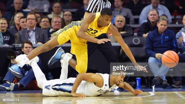 Jamal Cain of the Marquette Golden Eagles scrambles over Phil Booth of the Villanova Wildcats for a loose ball at The Wells Fago Center on January 6...