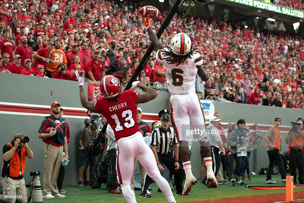 Jamal Carter, Sr. #6 of the Miami Hurricanes breaks up a pass intended for Bra'Lon Cherry #13 of the North Carolina State Wolfpack at Carter-Finley Stadium on November 19, 2016 in Raleigh, North Carolina. Miami won 27-13.