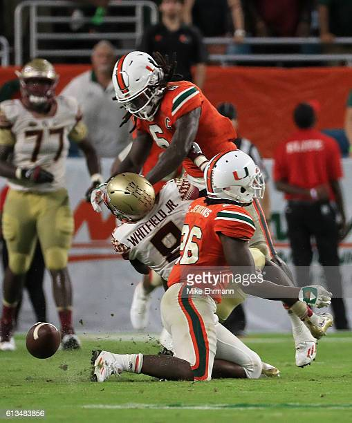 Jamal Carter Sr #6 of the Miami Hurricanes hits Kermit Whitfield of the Florida State Seminoles for a personal foul during a game at Hard Rock...