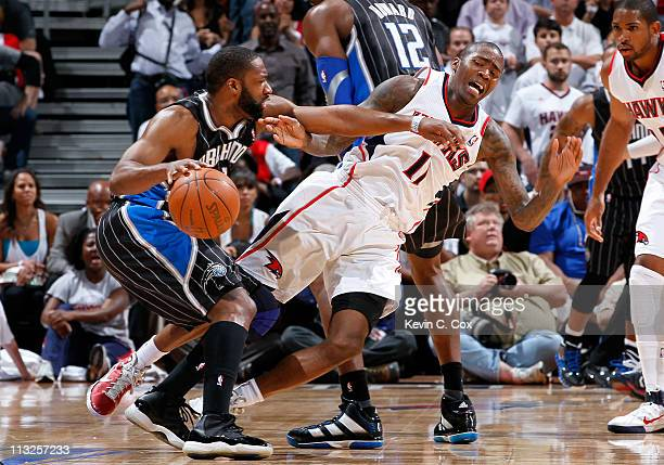 Jamal Crawford of the Atlanta Hawks draws an offensive foul as he is forced to the floor while defending against Gilbert Arenas of the Orlando Magic...
