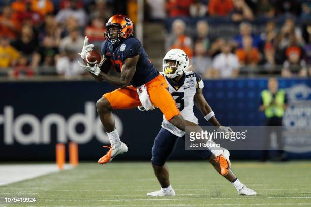 Jamal Custis of the Syracuse Orange catches the ball after committing pass interference against Toyous Avery Jr. #3 of the West Virginia Mountaineers...