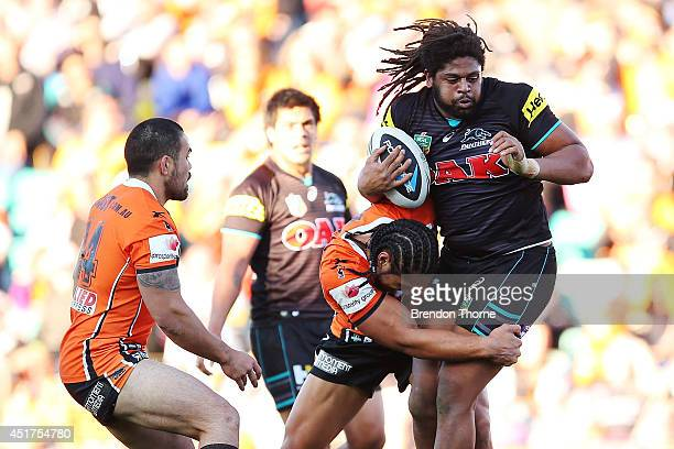 Jamal Idris of the Panthers is tackled by Martin Taupau of the Tigers during the round 17 NRL match between the Wests Tigers and the Penrith Panthers...