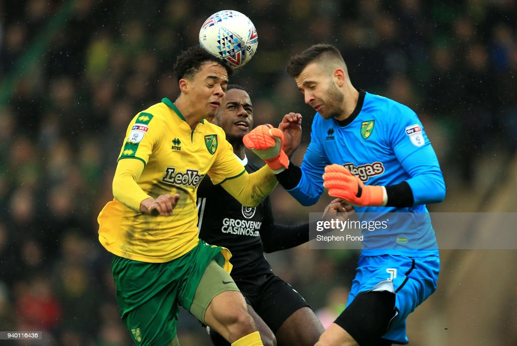 Jamal Lewis and Angus Gunn of Norwich City collide as Ryan Sessengnon of Fulham looks on during the Sky Bet Championship match between Norwich City and Fulham at Carrow Road on March 30, 2018 in Norwich, England.