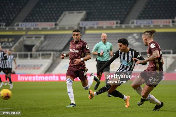 Jamal Lewis of Newcastle United crosses the ball as Raphinha and Kalvin Phillips of Leeds United defend during the Premier League match between...