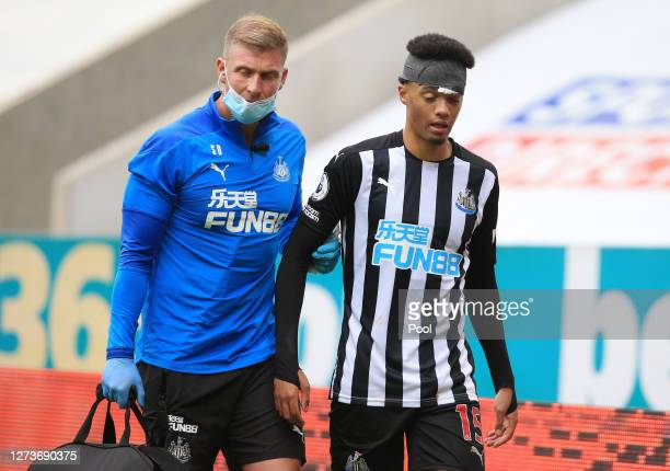 Jamal Lewis of Newcastle United leaves the pitch with the medical staff after being kicked in the face during the Premier League match between...