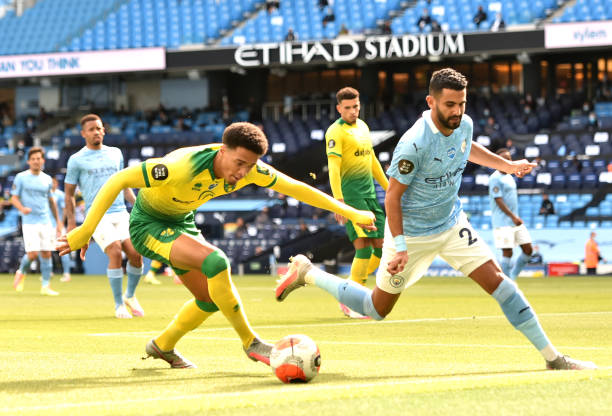 Jamal Lewis of Norwich City and Riyad Mahrez of Manchester City battle for the ball during the Premier League match between Manchester City and...