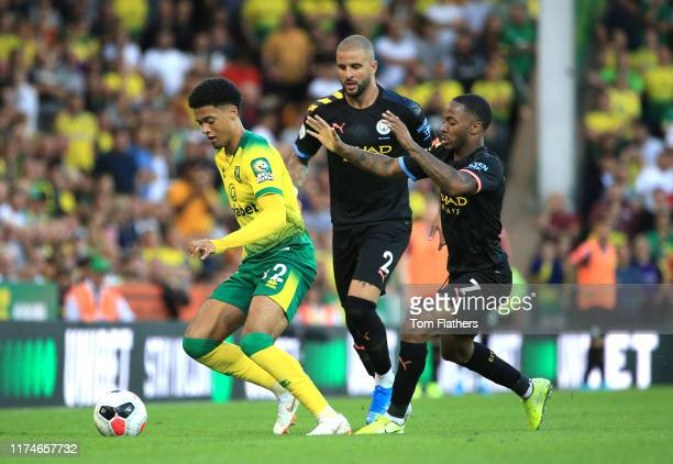 Jamal Lewis of Norwich City is challenged by Raheem Sterling of Manchester City during the Premier League match between Norwich City and Manchester...
