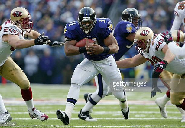Jamal Lewis of the Baltimore Ravens splits the San Francisco 49ers defense to rush for a first down on November 30 2003 at the MT Bank Stadium in...