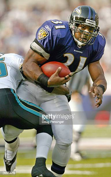 Jamal Lewis of the Baltimore Ravens who broke the1000 yard mark for the year tries to break the tackle of Fernando Bryant of the Jacksonville Jaguars...