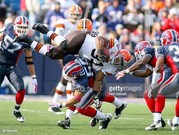 Jamal Lewis of the Cleveland Browns tries to jump over Keith Ellison of the Buffalo Bills at Ralph Wilson Stadium on October 11 2009 in Orchard Park...