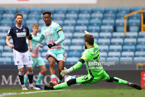 Jamal Lowe of Swansea City has a shot saved by Bartosz Bialkowski of Millwall FC during the Sky Bet Championship match between Millwall and Swansea...