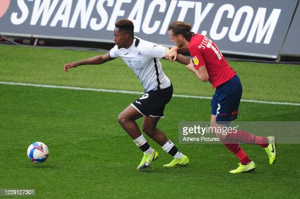 Jamal Lowe of Swansea City under pressure from Richard Stearman of Huddersfield Town during the Sky Bet Championship match between Swansea City and...