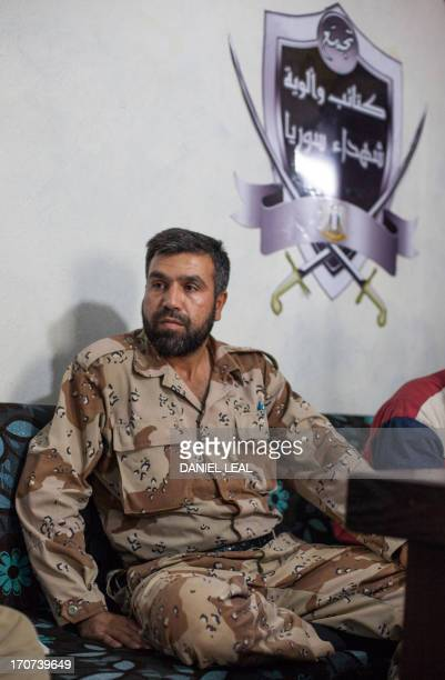 Jamal Maarouf commander of the Free Syrian Army's Syrian Martyrs' Brigade listens to a question during an interview with journalists at an...
