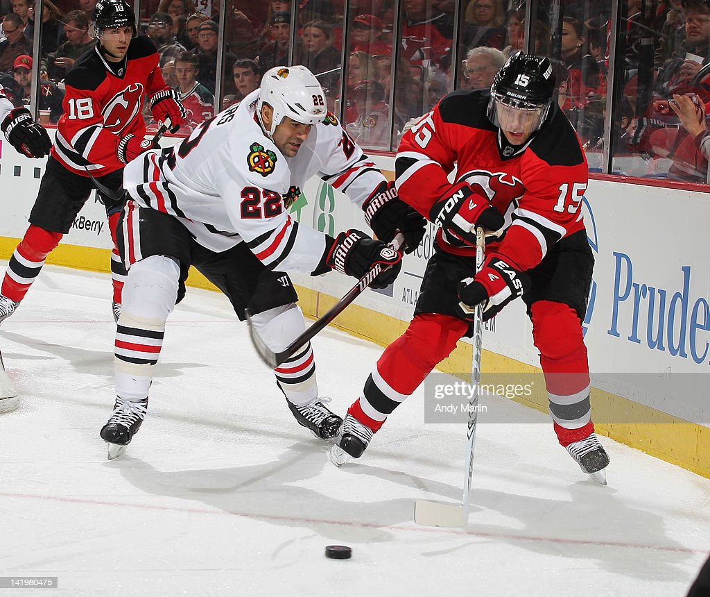 Jamal Mayers #22 of the Chicago Blackhawks and Petr Sykora #15 of the New Jersey Devils pursue a loose puck during the game at the Prudential Center on March 27, 2012 in Newark, New Jersey.