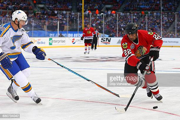 Jamal Mayers of the Chicago Blackhawks handles the puck against Al MacInnis of the St Louis Blues during the 2017 NHL Winter Classic Alumni Game at...