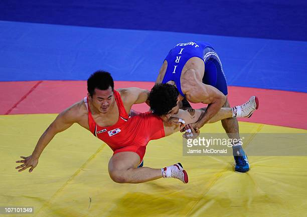 Jamal Mirzaei of Iran throws Jaesung Lee of Korea in the Men's Freestyle 84kg class Final at Huagong Gymnasium during day twelve of the 16th Asian...