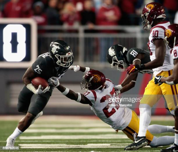 Jamal Morrow of the Washington State Cougars carries the ball against Aiene Harris of the USC Trojans in the second half at Martin Stadium on...