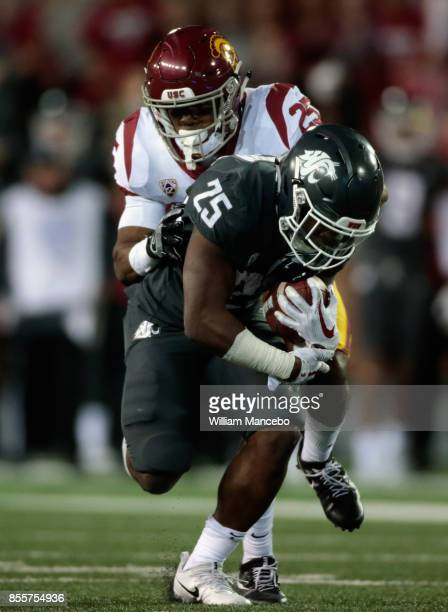 Jamal Morrow of the Washington State Cougars is tackled by Jack Jones of the USC Trojans in the second half at Martin Stadium on September 29 2017 in...
