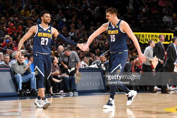 Jamal Murray and Nikola Jokic of the Denver Nuggets high five during the game against the New Orleans Pelicans on October 29 2018 at the Pepsi Center...