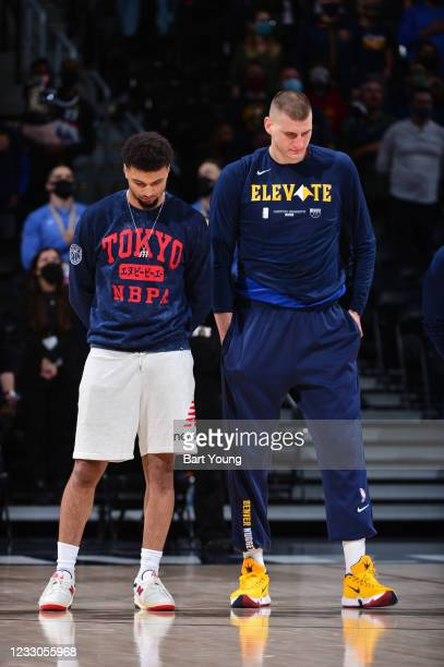 Jamal Murray of the Denver Nuggets and Nikola Jokic of the Denver Nuggets listen to the national anthem before the game against the Portland Trail...
