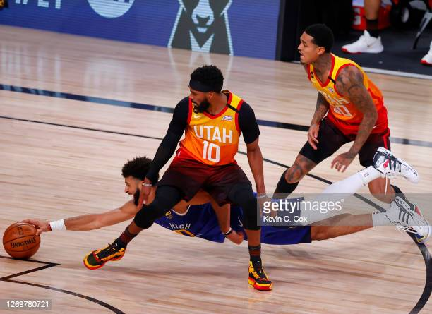 Jamal Murray of the Denver Nuggets dives to grab a loose ball against Mike Conley and Jordan Clarkson of the Utah Jazz during the fourth quarter in...