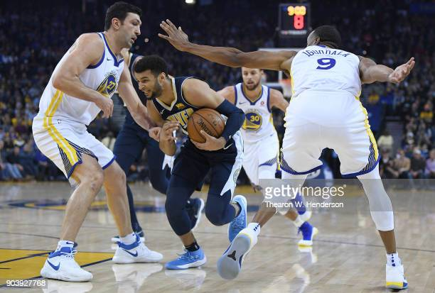Jamal Murray of the Denver Nuggets drives to the basket on Zaza Pachulia Andre Iguodala of the Golden State Warriors during an NBA Basketballl game...