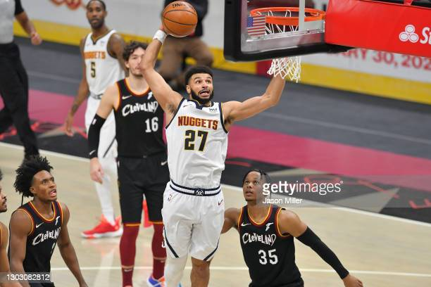 Jamal Murray of the Denver Nuggets dunks over Isaac Okoro of the Cleveland Cavaliers during the fourth quarter at Rocket Mortgage Fieldhouse on...