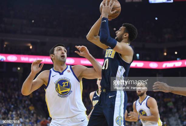 Jamal Murray of the Denver Nuggets goes up to shoot over Zaza Pachulia of the Golden State Warriors during an NBA Basketballl game at ORACLE Arena on...