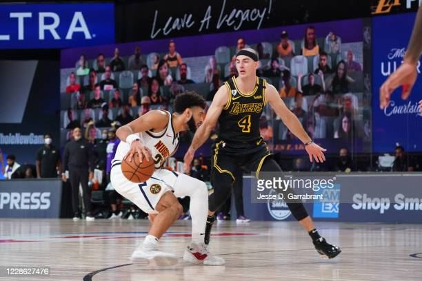 Jamal Murray of the Denver Nuggets handles the ball against Alex Caruso of the Los Angeles Lakers during Game Two of the Western Conference Finals of...