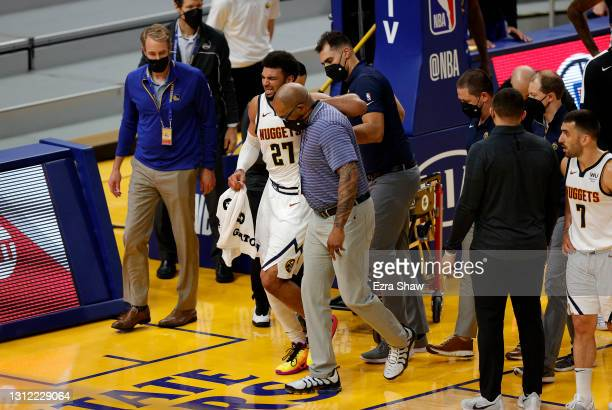 Jamal Murray of the Denver Nuggets is helped off the court after an injury in their game against the Golden State Warriors at Chase Center on April...