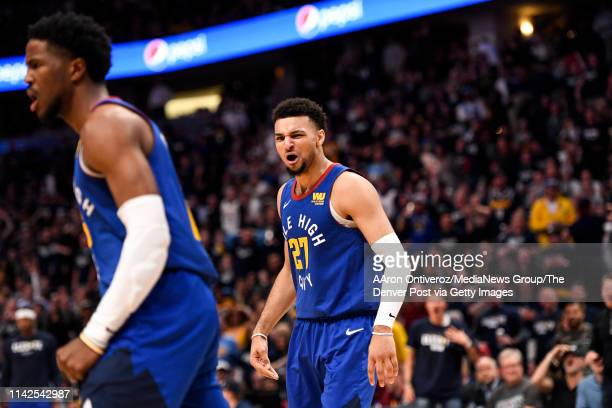Jamal Murray of the Denver Nuggets reacts to a violent dunk by Malik Beasley on Davis Bertans of the San Antonio Spurs during the third quarter of...