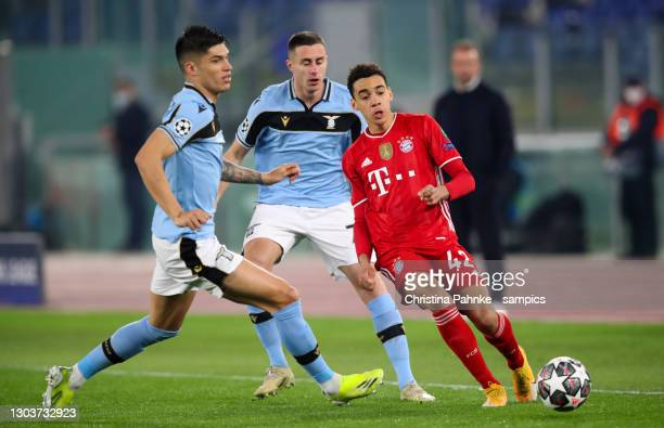 Jamal Musiala of Bayern Muenchen vies with Andreas Pereira of Lazio Roma during the UEFA Champions League Round of 16 match between Lazio Roma and...