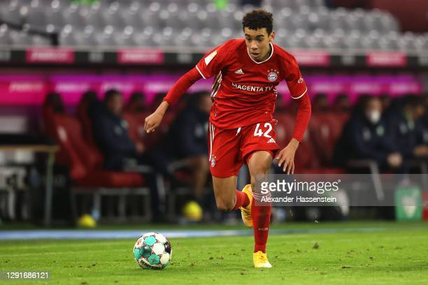 Jamal Musiala of FC Bayern München runs with the ball during the Bundesliga match between FC Bayern Muenchen and VfL Wolfsburg at Allianz Arena on...