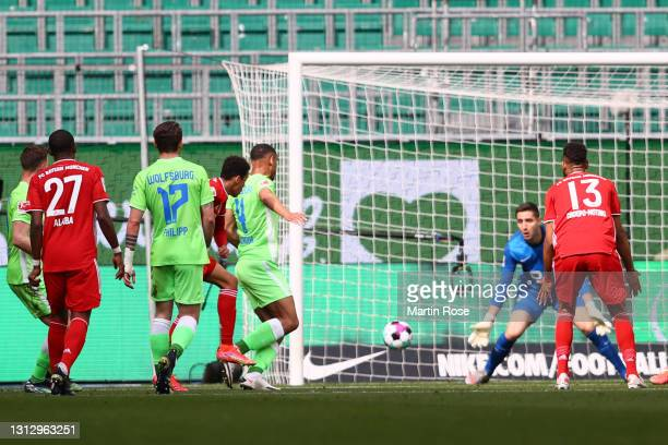 Jamal Musiala of FC Bayern Muenchen scores his team's first goal during the Bundesliga match between VfL Wolfsburg and FC Bayern Muenchen at...