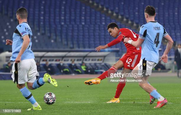 Jamal Musiala of FC Bayern Muenchen scores their sides second goal under pressure from Patric of S.S. Lazio during the UEFA Champions League Round of...