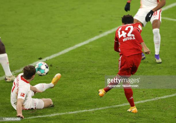 Jamal Musiala of FC Bayern Munich scores his team's first goal during the Bundesliga match between FC Bayern Muenchen and RB Leipzig at Allianz Arena...