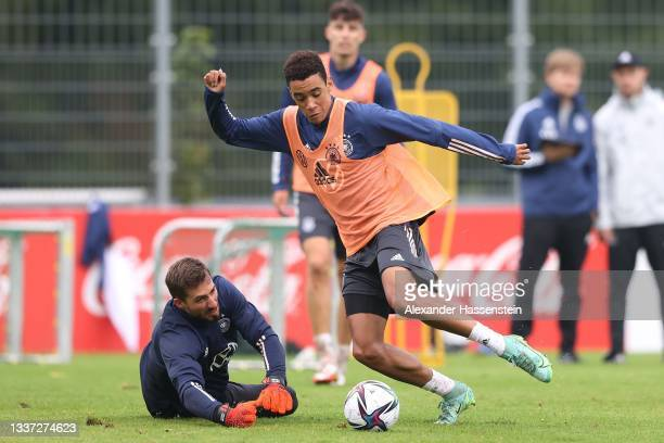 Jamal Musiala of Germany battlef for the ball with keeper Kevin Trapp during a training session at ADM-Sportpark on August 30, 2021 in Stuttgart,...