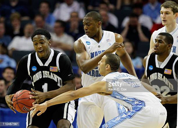 Jamal Olasewere of the Long Island Blackbirds moves the ball between Justin Knox and Kendall Marshall of the North Carolina Tar Heels in the first...