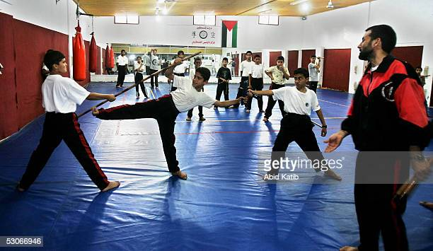 Jamal Oqeli a Palestinian trainer teaches boys how to practise martial arts by Nunchaku at The Palestinian Nunchaku Union headquarters June 14 2005...