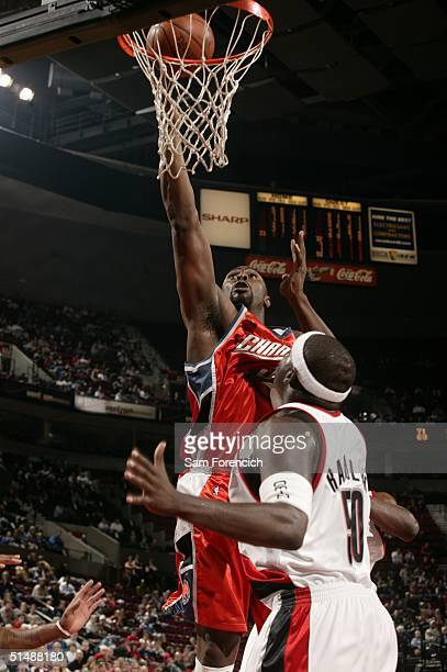 Jamal Sampson of the Charlotte Bobcats makes a basket as Zach Randolph of the Portland Trail Blazers looks on during a game at the Rose Garden Arena...