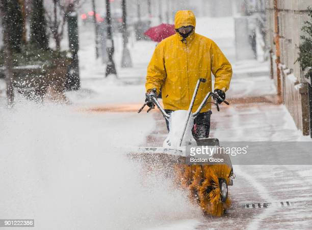 Jamal Talai pushes a snow blower through snow along Commonwealth Avenue during a winter storm in Boston on Jan 4 2018