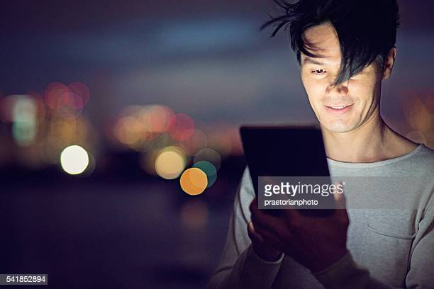 Jamanese man with tablet in the the night