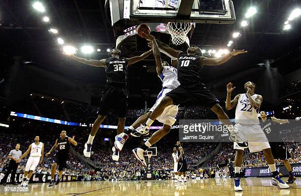Jamar Samuels and Victor Ojeleye of the Kansas State Wildcats block a shot by Thomas Robinson of the Kansas Jayhawks during the finals of the 2010...
