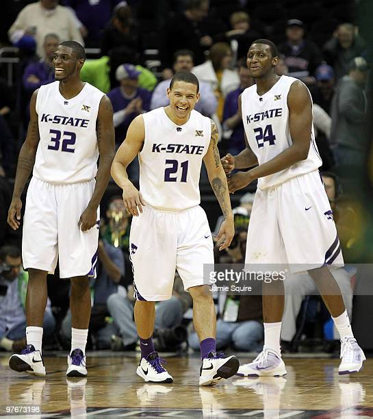 Jamar Samuels, Denis Clemente, and Curtis Kelly of the Kansas State Wildcats celebrate as the Wildcats defeat the Baylor Bears 82-75 to win their...